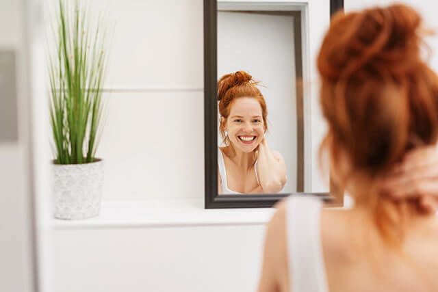 woman looks in mirror