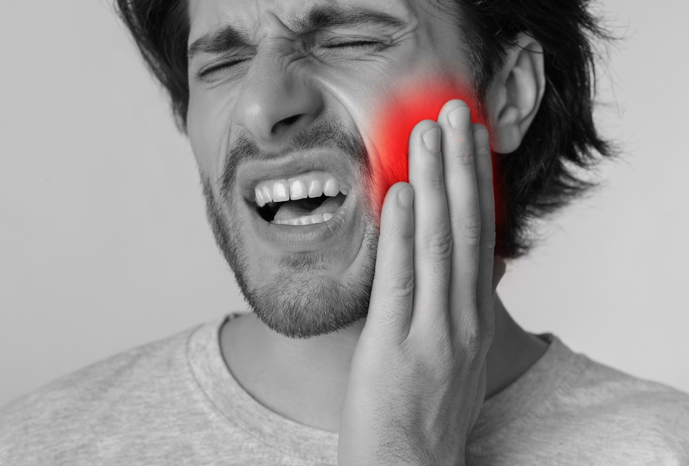 man holding cheek in pain from severe toothache